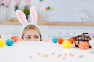 Cute little girl with white bunny ears looking at camera while peeking out from behind table with colorful Easter eggs. photo