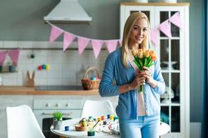 Woman holding flowers in decorated kitchen. photo