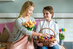 los niños juegan en la cocina y sostienen una canasta de huevos de Pascua. foto