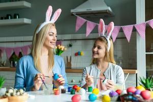 mamá con hija en orejas de conejo pinta huevos de pascua en la cocina. foto