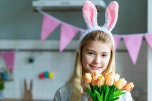 niña en la celebración de tulipanes en orejas de conejo blanco en las manos. adorable niña sonriente sosteniendo flores. foto