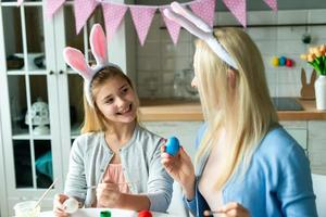 Close up of smiling daughter looking at mom who is painting easter egg. photo