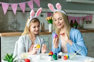 Mother and her daughter paint eggs. They wear the hare's ears photo