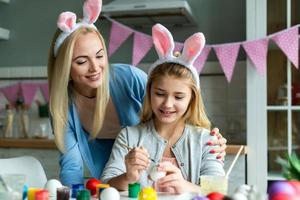 Happy Easter atmosphere. Funny, pretty mom making control, looking how her cute, small, joyful daughter draw, paint, decorate easter eggs, together wearing bunny ears photo