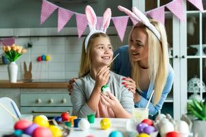 Happy holiday. A mother and her daughter are painting eggs. Family preparing for Easter. Cute little child girl is wearing bunny ears. photo