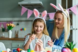 Funny, cheerful, joyful mum teaching, training her cute, pretty, small, little daughter draw, paint, decorate easter eggs, together wearing bunny ears, preparing for Easter photo
