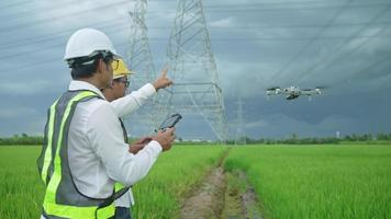 Two electrical engineers in yellow safety helmets Drones are being used to inspect high-powered electric poles. located in a vast grassland video