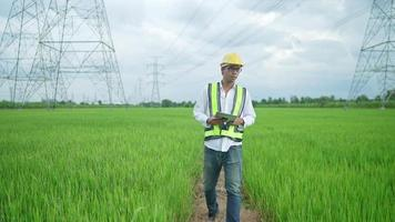 Font View.Electrical engineer wearing a Yellow helmet and safety carrying using tablet vest walking near high voltage electrical lines towards power station on the field. video