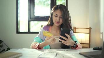 ralenti d'une jeune femme asiatique tenant un smartphone et une carte de crédit video