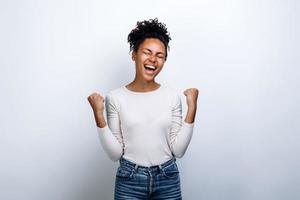 Victorious gesture. The girl on a background of a white wall rejoices in the victory photo