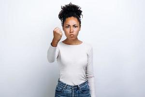 Young girl on white background shows his fist. Female force. photo