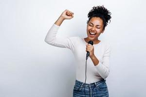 Cute girl sings into a microphone, has fun singing on a white background photo