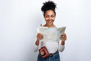 Beautiful, cheerful young woman holding a map and camera on a white wall background photo