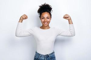 Portrait of Young cute sporty smiling woman while she shows her arms and biceps on camera photo