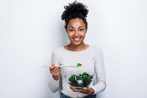 The girl poses with a homemade dish in the center on a white wall photo