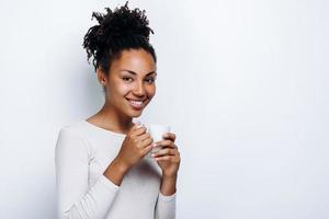 Portrait of happy woman thinking and looking into camera on white background photo