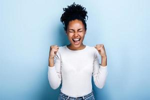 Happy young african girl make winner gesture posing isolated over blue background photo