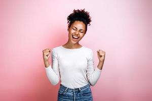 Overjoyed african American millennial girl isolated on pink studio background triumph get good news. Winner concept photo