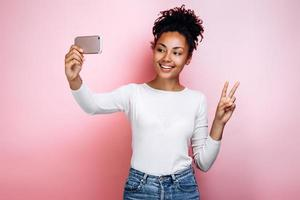 Attractive girl on a background of a pink wall makes a selfie photo