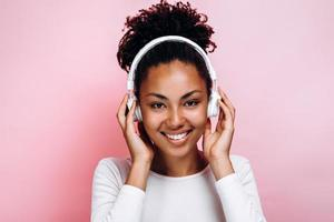 Attractive young afro american woman on pink background photo
