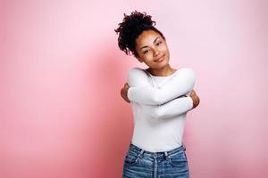 retrato, de, un, bastante, niña joven, abrazar, posición, aislado, en, fondo rosa foto