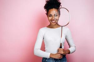 Beautiful, smiling girl stands on a background of a pink wall, covers her face with a racket photo