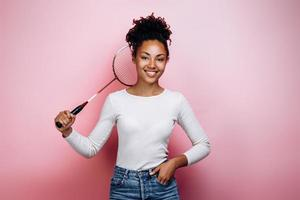 Girl holding a badminton racket on a background of a pink wall photo