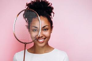 juguetona, niña, tenencia, raqueta de tenis foto