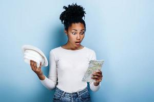 Shocked dark-skinned girl with a map and a hat in her hands isolated on a blue background photo