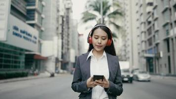 Asian businesswoman listening to music while walking in the street video