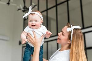 A young, pretty woman raises her tiny daughter. Little girl smiling happily photo