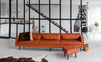 Stylish apartment, open space, in the middle of the room is a modern, beautiful sofa photo