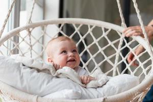 Hermosa niña columpiándose en una silla colgante en el dormitorio con su mamá foto