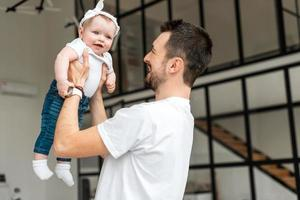 A young man hold her tiny daughter. Little girl smiling happily photo