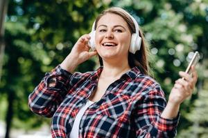 Charming, modern woman in white, wireless headphones having fun outdoors photo