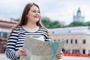 Mujer joven vestida con un suéter a rayas, con un mapa en sus manos, al aire libre, camina por las calles de la ciudad foto