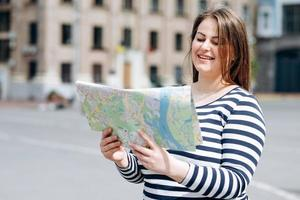 Young joyful woman with tourist map in hands enjoying beautiful strolling during her spring journey, happy female with cute smile studying atlas before walking in foreign city during summer trip photo