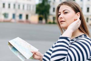 Travel girl visiting city with map in her hands and looking around. Happy cheerful female tourist exploring new city looking to the side. photo