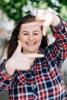Retrato de mujer caucásica hermosa juguetona que finge tomar una foto con sus manos mientras camina en la calle. modelo atractivo posando, usando las manos para hacer un marco al aire libre