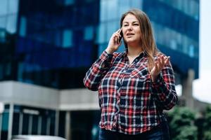 Pretty, business woman in a checkered shirt communicates on the phone on the background of the business center photo