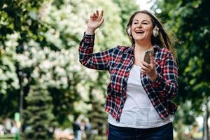 Beautiful woman with long hair, in a checkered shirt, in headphones, with a smartphone in her hands outdoors, having fun, jumping photo