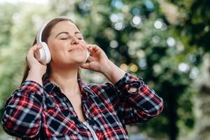 Happy girl enjoys the music coming from the headphones. photo