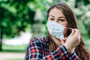 Beautiful woman takes off protective mask outdoors photo