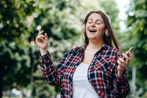 Modern girl has fun singing on a background of nature photo