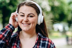 Young woman wearing headphones with a happy face standing in the middle of the park photo