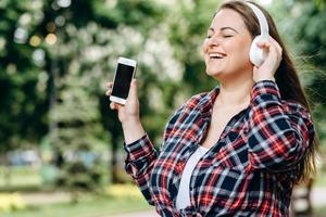 Beautiful, attractive brunette enjoys a favorite song that comes from headphones. photo