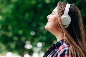Face profile of a pretty, relaxed woman in headphones on a background of nature, photo