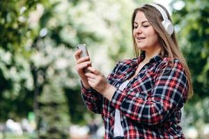 Beautiful, woman with long hair, in a checkered shirt, in headphones, with a smartphone in her hands outdoors photo