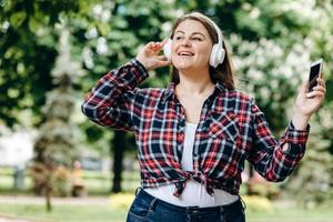 Cute, smiling, cheerful girl plus size, sings her favorite song while walking outdoors photo