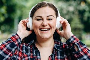 Adorable lady in standing in city and listening to favorite song in headphones. Outdoor portrait of dreamy european girl wears white earphones. photo